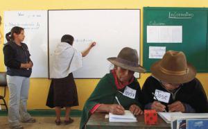 en avant-plan, deux femmes écrivent sur une table, alors qu'une femme en arrière-plan écrit sur un tableau blanc pendant qu'un femme l'observe