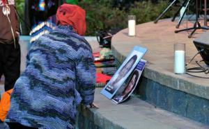 Une femme se recueuille devant les photos de femmes autochtones