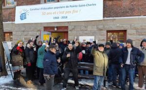Plusieurs personnes devant l'édifice du Carrefour lèvent leur verre