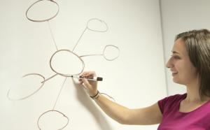une femme trace un réseau sur un tableau blanc
