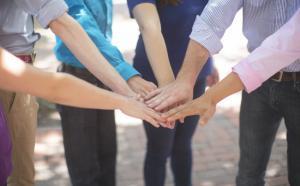 Gros plan sur des personnes qui réunissent leurs mains.