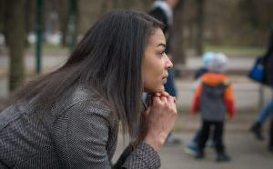 vue de profil d'une femme assise, le menton appuyé sur ses mains