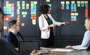 une femme debout anime une réunion devant un mur remplie de pense-bête de couleurs différente. Deux personnes sont assises