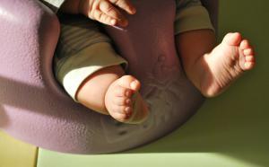 Photographie en gros plan sur les pieds d'un poupon assis sur un siège d'appoint.