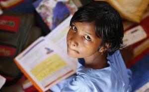 Un enfant assis par terre avec un livre, regard l'objectif de la caméra.
