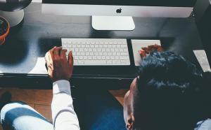 Vue de dos d'une personne qui travaille sur un ordinateur.