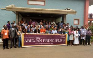 une foule devant un édifice tenant la banderole The Abidjan Principles