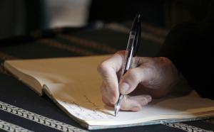 Gros plan sur une main qui écrit dans un cahier.