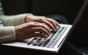 Photographie en gros plan sur les mains d'une personne travaillant sur un ordinateur portable.