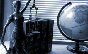 La statue de la justice sur une table, à gauche d'un globe terrestre.