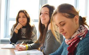 Photographie de trois étudiantes en salle de classe.