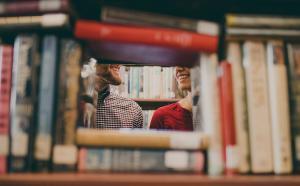 à travers des livres d'une étagère, nous voyons deux étudiants qui se sourient