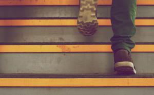 Gros plan sur des pieds qui montent des escaliers.