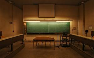 Photographie d'une petite salle de classe vide et sombre.