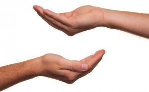 Deux mains tendus, superposées sur fond blanc.