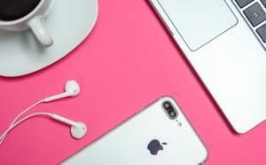 Sur une table rose, on voit partiellement un café, un ordinateur portable, un téléphone intelligent et ses écouteurs.