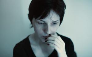 Une femme la tête légèrement penchée, l'air pensive, la main droite portée à sa bouche.