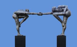 Photographie d'une statue extérieure de deux personnes se tenant sur une jambe, penchées, se faisant face et se tenant par la main.