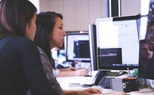 Deux personnes travaillent à l'ordinateur.