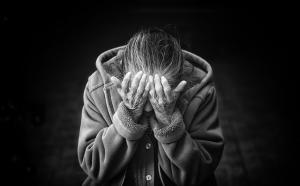une femme âgée se cache le visage