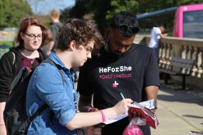Une personne signe une feuille tenu par une personne portant un chandail HeForShe.