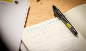 """Gros plan d'un carnet ouvert avec un stylo au milieu. Dans le carnet, il est écrit """"Lancement Jobready""""."""