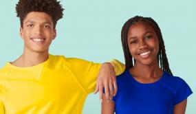Deux personnes sourient à la caméra, l'une appuyant son coude sur l'épaule de l'autre.