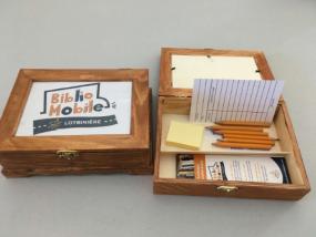 Photographie de boîtes du projet contenant des crayons, des fiches de prêt et de signets.