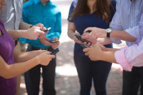 Un cercle de personnes tenant des téléphones portables.