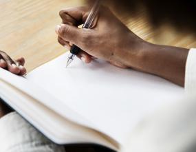 Gros plan sur la main d'une personne qui écrit dans un carnet.