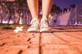 Vue sur les souliers d'une personne debout avec une ville en arrière plan.