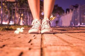 Photographie en gros plan sur les pieds d'une personne debout dans un milieu urbain.