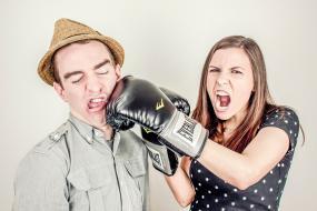 Une femme portant des gants de boxes frappe au visage un homme à son côté.