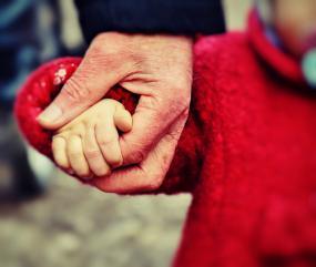 Gros plan sur une main d'adulte qui tient une main d'enfant.