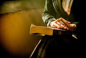 Gros plan sur des mains d'une personne âgée qui reposent sur un livre qui repose sur ses genoux.