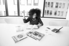 Photographie en noir et blanc d'une personne assise à une table avec plusieurs livres devant elle. Un ordinateur portable et un téléphone intelligent repose également sur la table.