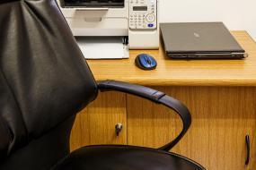 Une chaise devant un bureau où se trouve une imprimante et un ordinateur portable.