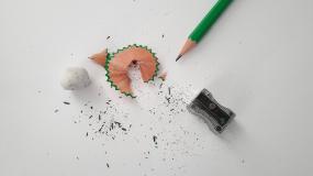 Photographie d'un crayon posé à côté d'un aiguisoir et de retailles de crayon.