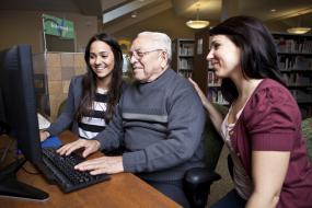 une personne âgée travaille à l'ordinateur, avec deux autres personnes à ses côtés