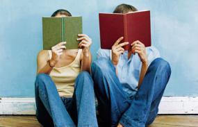 Photographie de deux personnes, assises par terre, tenant un livre devant leur visage.