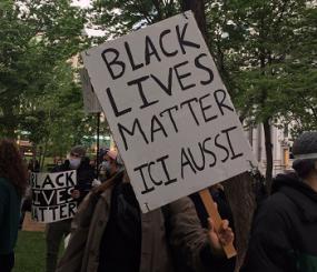 """Vu sur des personnes à une manifestion. En premier plan, Une personne tient une pancarte devant son visage où il est écrit en noir """"Black Lives Matter ici aussi""""."""