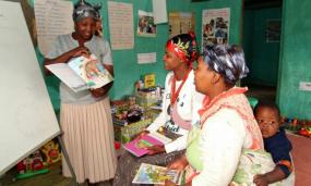Une enseignante pointe une image dans un livre pour deux femmes devant elle.