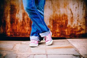 Gros plan sur les jambes d'une personne debout, dont les jambes sont croisées.