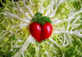 Un poivron coupé en forme de coeur est déposé au milieu sur le coeur d'une salade ouverte.