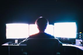 un homme de dos à contrejour de trois écrans d'ordinateur
