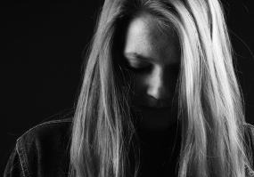 Photographie en noir et blanc d'une personne, la tête légèrement perchée vers l'avant et les cheveux dans le visage.