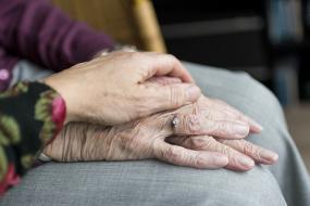 Gros plan d'une main qui repose sur des mains âgées.