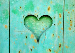 Un coeur sculpté dans une planche de bois turquoise.