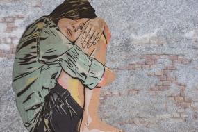 Oeuvre d'art, murale d'une personne assise, se tenant les genoux contre elle.