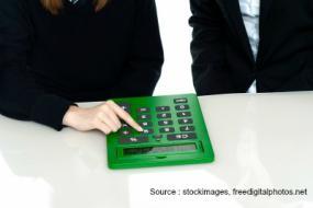 Gros plan sur deux personnes devant une calculatrice verte. l'une des personnes l'utilise.